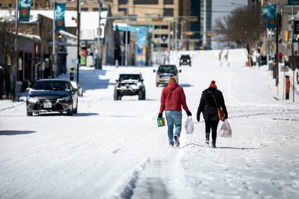 Des personnes marchent au milieu d'une rue enneigée, portant des sacs de provisions, à Austin, au Texas, le 15 février