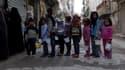 Des enfants attendent de recevoir des rations de nourriture, dans la banlieue d'Alep, en Syrie, en novembre 2014.