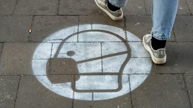 Un marquage au sol sur un trottoire appelle au port du masque - Image d'illustration