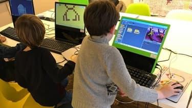 De jeunes enfants en plein apprentissage sur les ordinateurs Pi-top.