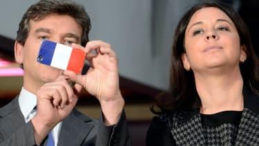 Arnaud Montebourg utilise son téléphone portable à côté de la ministre de l'Artisanat, du Commerce et du Tourisme Sylvia Pinel le 24 octobre 2013.