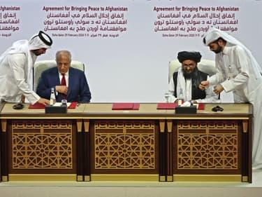 Le représentant des Etats-Unis pour la paix en Afghanistan, Zalmay Khalilzad, et le chef militaire afghan Mullah Abdul Ghani Baradar signent un accord de paix à Doha, au Qatar, le 29 février 2020
