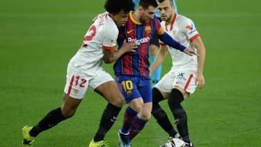Lionel Messi pris en tenaille par les joueurs sévillans Jules Koundé (à gauche) et Jordan (à droite), en demi-finale aller de la Coupe d'Espagne, le 10 février 2021 à Séville