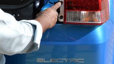 Un employé de la compagnie d'Etat Carzonrent branche une Mahindra Reva électrique, en 2013.