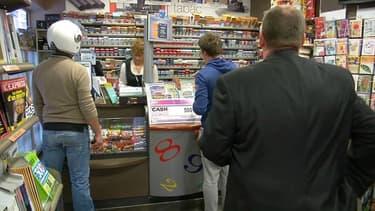 Des joueurs dans un bar-tabac viennent chercher leur ticket à gratter ou faire leur loto.