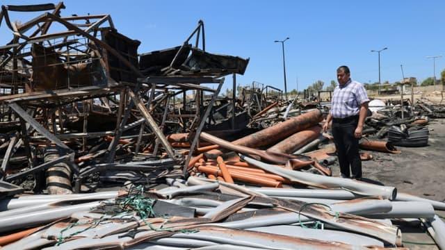 Le propriétaire palestinien  de l'usine de plastique Siksik devant les tuyaux carbonisés par les frappes israéliennes à Gaza, le 23 mai 2021