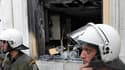 Policiers devant un immeuble abritant une agence bancaire à Athènes, qui a pris feu après avoir été la cible de cocktails Molotov, mercredi. Trois personnes ont péri dans cet incendie en marge des manifestations contre le plan d'austérité négocié par le g
