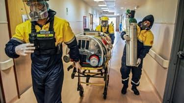 """Un patient atteint du coronavirus arrive à l'unité de soins intensifs de l'hôpital Rebagliati, à Lima, après avoir été transporté dans une """"capsule de sécurité"""" à bord d'un avion-ambulance depuis l'aéroport d'Iquitos, le 1er septembre 2020 au Pérou"""