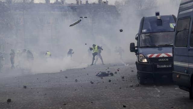 Des manifestants jetant des pavés sur des cars de CRS, sous l'arc de Triomphe
