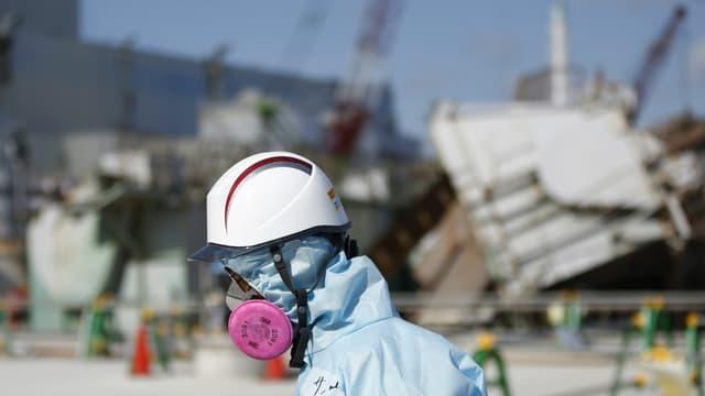 Un employé de Tepco devant le réacteur n°1 de la centrale nucléaire Fukushima Daiichi, le 10 février 2016.