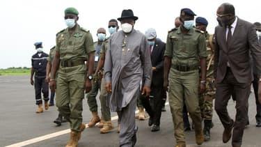 L'ancien président nigérian Goodluck Jonathan, chef de la délégation ouest-africaine envoyée au Mali, à côté de Malick Diaw, vice-président du Comité national pour le salut du peuple, à l'aéroport de Bamako, le 22 août 2020
