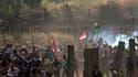 Des manifestants palestiniens et syriens fuient pour s'abriter des gaz lacrymogènes tirés par les soldats israéliens dimanche sur le plateau du Golan, près de la frontière entre la Syrie et Israël. La Syrie a porté lundi à 23 morts le bilan de cette manif