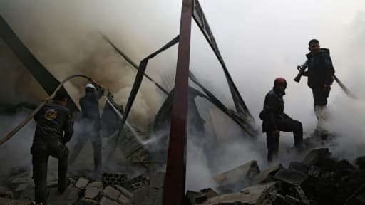 Des Casques blancs syriens éteignent un incendie provoqué par des frappes aériennes du régime sur la ville rebelle de Hamouria, dans les environs de Damas, le 21 mars 2017