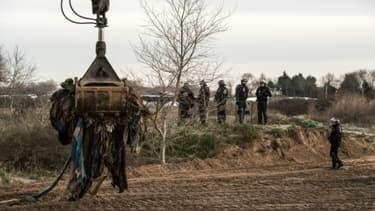 """Un bulldozer est à l'oeuvre le 18 janvier 2016 dans le camp de """"la Jungle"""", à Calais, dans le nord de la France"""