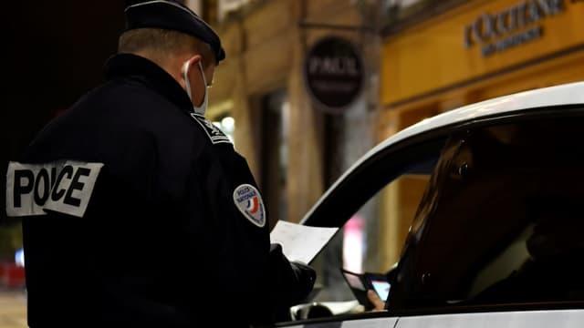 Un policier vérifie une attestation le 5 janvier 2021 à Metz, placé sous couvre-feu à partir de 18h00