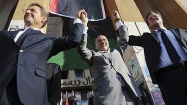 Nicolas Sarkozy et le Premier ministre britannique David Cameron (à droite) accueillis en héros à Benghazi, mi-septembre, par le chef du Conseil national de transition libyen, Moustapha Abdeljalil. Trois ans après la réception de Mouammar Kadhafi à l'Elys