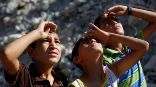 Des enfants palestiniens en train d'observer un avion de l'armée israélienne dans le nord de la bande de Gaza, le 4 août