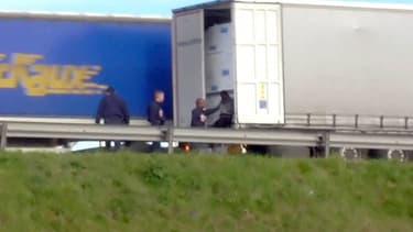 Des CRS évacue un migrant d'un camion