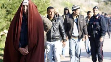 Des immigrants illégaux tunisiens encadrés par la police italienne à leur arrivée sur l'île de Lampedusa. La surveillance de la frontière franco-italienne a été renforcée pour faire face à l'éventuelle arrivée en France de réfugiés tunisiens venus d'Itali