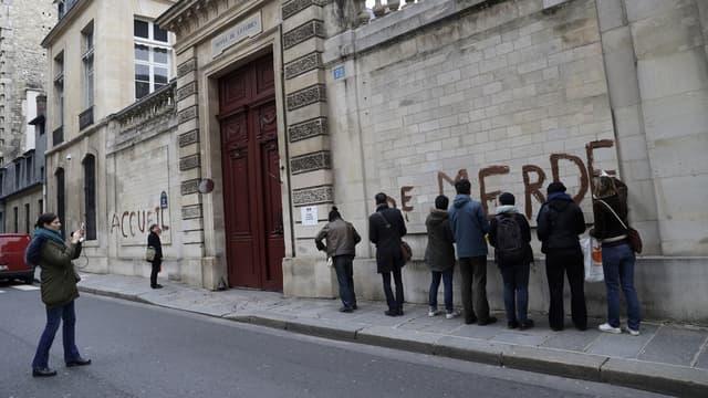 Les mains recouvertes de gants en latex, chacun des militants a dessiné une lettre en capitale sur le mur de pierre