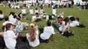 Des jeunes engagés dans le service civique discutent, assis sur la pelouse du Champs-de-Mars, à Paris le 27 juin 2012