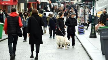 Des habitants marchent dans une rue piétonne de Paris, au premier jour d'un nouveau confinement partiel dans la capitale française à cause de la pandémie de Covid-19, le 20 mars 2021