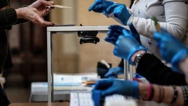 Photo dans un bureau de vote de Lyon le 15 mars, lors du premier tour des élections municipales - JEFF PACHOUD / AFP