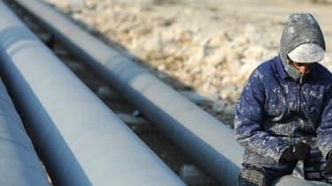 Un ouvrier travaillant sur un pipeline, image d'illustration.