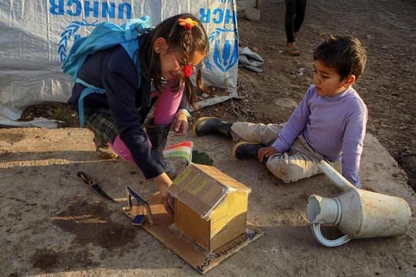 Photo prise par un stagiaire: deux enfants jouent par terre.
