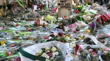 Des fleurs déposées en hommage à Samuel Paty devant son collège à Conflans-Sainte-Honorine, le 17 octobre 2020