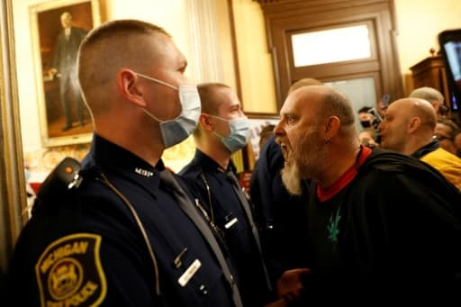 Un manifestant anti-confinement crie sur des policiers au siège du Parlement du Michigan, à Lansing, le 30 avril 2020