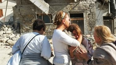 Une femme pleure devant des maisons effondrées dans le village d'Illica, près d'Accumoli, au lendemain du séisme qui a frappé l'Italie.