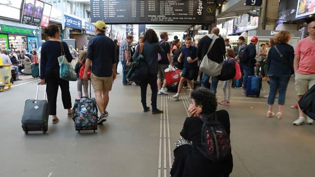 Des voyageurs attendent leur train le 30 juillet 2017 à la gare Montparnasse, à Paris, après une panne