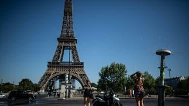 Rafraichissement grâce à une fontaine à Paris près de la Tour Eiffel, le 7 août 2020