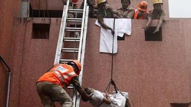 Evacuation d'un patient par des pompiers dans un hôpital de Calcutta, dans l'est de l'Inde. Un incendie a ravagé vendredi cet établissement de sept étages, faisant au moins 84 morts, en majorité des patients qui dormaient lorsque le sinistre s'est déclaré
