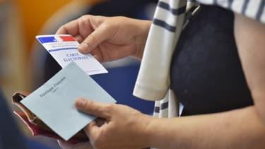 Une femme, carte électorale et enveloppe de vote à la main (Photo d'illustration).