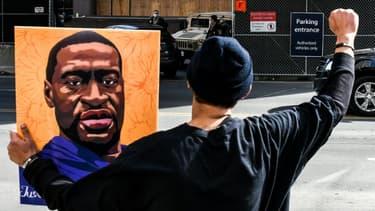 Un manifestant tient le portrait de George Floyd devant le tribunal de Minneapolis, le 9 mars 2021 dansle Minnesota