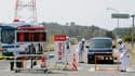 """Des policiers postés à la limite du périmètre d'évacuation de 20 km autour de la centrale nucléaire de Fukushima-Daiichi renseignent des habitants quittant ce secteur (les panneaux indiquent """"route bloquée"""" et """"entrée non autorisée""""). Cette zone autour de"""
