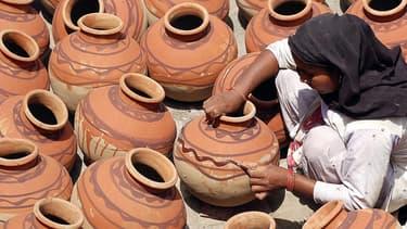 Une indienne met la dernière touche à des pots servant à conserver les aliments.
