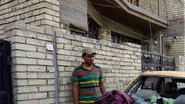 Une voiture endommagée sur le site de l'attentat suicide revendiqué par l'EI et qui visait les musulmans chiites le 15 octobre 2016, dans un quartier de Bagdad.
