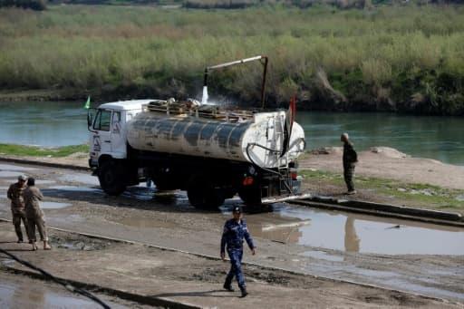 Des soldats irakiens surveillent le remplissage en eau d'un camion-citerne, le 1er avril 2017 à Hamman al-Alil