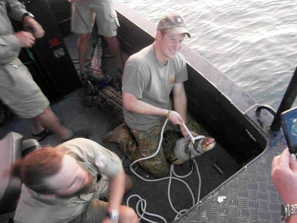 Le prince Harry assis fièrement sur le crocodile qu'il vient de capturer.