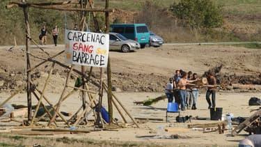 """Des opposants au barrage de Sivens près de leurs barricades avec sur une pancarte la mention: """"Carcenac (nom du président du conseil général du Tarn), il y a du sang sur ton barrage""""."""