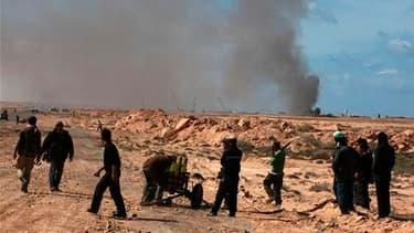 Des insurgés préparent leurs roquettes pour répliquer à un tir de mortier de l'armée dans l'Est libyen. La situation est toujours confuse en Libye, où des tirs ont été entendus dimanche à Tripoli, tandis que le régime de Mouammar Kadhafi affirme avoir rep