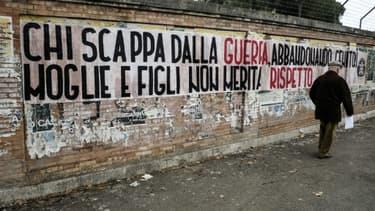 Un homme marche à côté d'une banderole déployée par un groupe d'extrême droite italien le 31 janvier 2017 à Rome